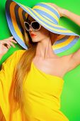 picture of beautiful lady  - Beautiful fashionable lady wearing bright yellow dress over green background - JPG