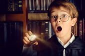 pic of fairies  - Surprised boy stands with watch in the library with many old books - JPG