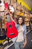 picture of ukulele  - Girl is holding red ukulele in music shop - JPG