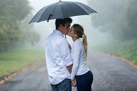 picture of hand kiss  - loving young couple in love under umbrella in the rain - JPG