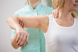 picture of therapist  - Physical therapist diagnosing patient with painful arm - JPG