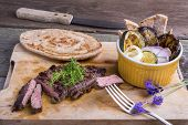 picture of cheval  - Provencal style horse meat entrecote steak with ratatouille and flat bread served on a wooden board decorated with lavender and fresh thyme - JPG