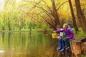 image of pole  - Happy kids sitting and fishing together near the pond with colorful fishing poles in beautiful forest landscape - JPG