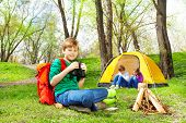 stock photo of binoculars  - Happy boy with red backpack and binocular  near the wooden bonfire and yellow tent during camping in summer weather - JPG