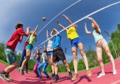 stock photo of volleyball  - View from below of teens playing volleyball on the game court together outside during summer sunny day - JPG