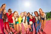 stock photo of volleyball  - Row of happy teens standing on the volleyball game court holding ball during summer sunny day - JPG