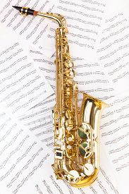 stock photo of musical scale  - Shiny golden alto saxophone in full size on the musical notes background with standard scales exercises - JPG