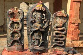 picture of serpent  - Devotees put vermilion on idols of serpent gods at Yoga Narasimha Temple in Nandi Hills near Bengaluru Karnataka India Asia - JPG