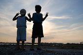 Crianças, apontando, pôr do sol, céu e nuvens na zona rural