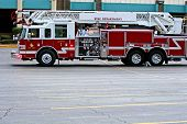 stock photo of firehose  - A red firetruck on the scene in a parking lot - JPG