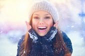 Winter young woman portrait. Beauty Joyful  Model Girl touching her face skin and laughing, having f poster