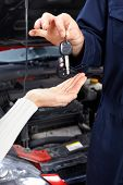picture of car repair shop  - Handsome mechanic inspecting the tire pressure in auto repair shop - JPG