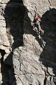image of sling bag  - A rock climber works his way up a rock face protected by a rope clipped into bolts - JPG