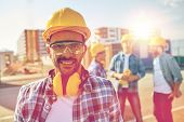 business, building, teamwork and people concept - smiling builder with hardhat and headphones over g poster