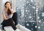people, winter, christmas and teens concept - sad unhappy pretty teenage girl sitting on windowsill  poster