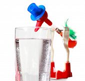 Red toy in blue hat dips by big beak into water in transparent glass
