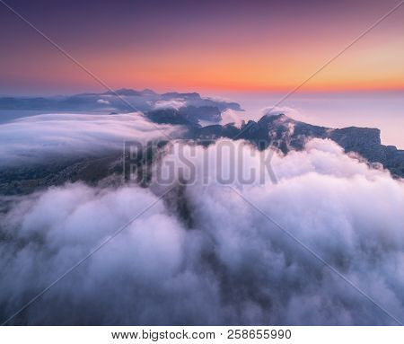 poster of Aerial View Of Low Clouds, Mountains, Sea And Colorful Sky At Sunset. Above The Clouds At Dusk. Seas