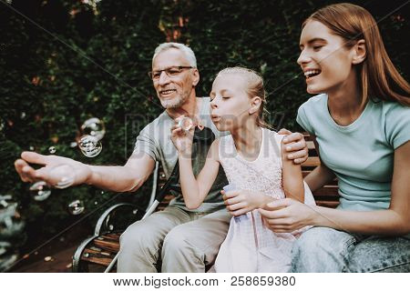 poster of Elderly Man Is Sitting On A Bench. Next To His Crutch. He Is Seen By A Woman With A Girl. They Are S