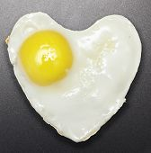 Fried egg like heart on frying pan.