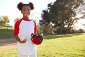Young Black girl holding baseball and mitt looking to camera poster