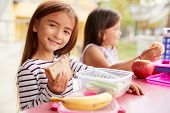 Elementary school girls eating at school lunch table poster