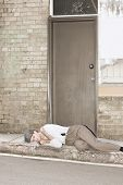 image of eviction  - A Newly Evicted Homeless Man Sleeps On The Kerbside - JPG