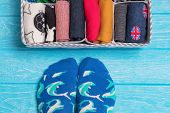 Box With Different Colorful Socks. Feet Selfie And A Socks Organizer On A Blue Background. Top View, poster