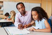 Teacher working with elementary school girl at her desk poster