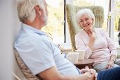 Senior Couple Sitting In Chairs And Chatting In Retirement Home poster