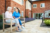 Senior Woman Sitting On Bench And Talking With Nurse In Retirement Home poster