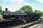 Old Steam Locomotive On Railroad Station. Vintage Steam Railway Road. Old Locomotive On Station Uk R poster