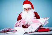Portrait of confused Santa Claus holding letters and looking at them in trouble