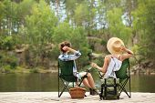 Young Friends Resting On Pier Near Lake. Camping Season poster