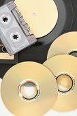 Dvd Discs, Audio Cassettes And Vinyl Record. Compact Discs, Audio Tape And Vinyl Plate Close Up, Ver poster