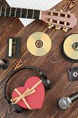 Set Of Audio Devices On Wooden Background. Compact Discs, Audio Cassettes, Acoustic Guitar, Music Pa poster