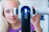optometry concept - pretty, young female patient having her eyes examined by an eye doctor (color to