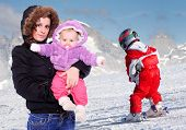 Young mother and her childs spent free time together on the snow.