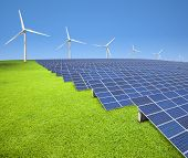 solar panels and wind turbines on the grass field