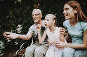 Elderly Man Is Sitting On A Bench. Next To His Crutch. He Is Seen By A Woman With A Girl. They Are S poster