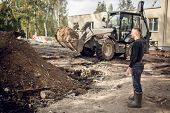 Man With Is As A Customer  On The Construction Site And  Modern Excavator That Performs Excavation W poster