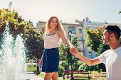 Happy Multiracial Couple Walking By Fountain In City. Man Holds His Girlfriends Hand. People Having poster