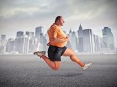 Fat man jogging with cityscape in the background
