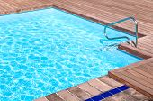 Wooden floor beside the blue swimming pool