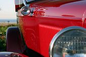 A partial shot of a red Hot Rod sits at a car show for all to see and dream of ownership of this neat car
