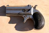 an antique 2 shot .45 cal derringer hand gun