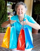 Senior woman addicted to shopping, holding up a handful of bags.
