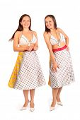 Two same women dressed in bikini and skirt smiles in studio on white background.