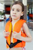 Little sorrowful girl wearing orange life-jacket looks at camera after swimming in pool.