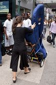 New York jul 28: Emily Hopkins transportiert ihre Harfe entlang 34th St zur Penn Station am 28. Juli 2012 in