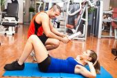 Woman training abdominal on the floor in the gym with a personal trainer